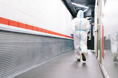 Healthcare man walking while wearing protective suit in hospital - PGF00109