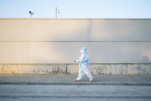 Nurse wearing protective wear while walking on footpath in city - PGF00121