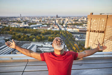 Happy bearded man with arms outstretched leaning back while standing on building terrace in city during sunset - FMKF06417
