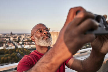Bearded mature man using smart phone for photographing sunset from rooftop in city - FMKF06423