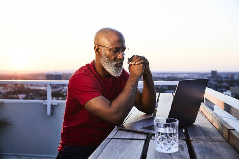 Mature bearded man looking at laptop while sitting on building terrace in city during sunset - FMKF06426