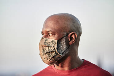 Bald man wearing protective face mask at rooftop against sky during pandemic - FMKF06441