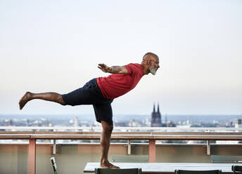Bald man balancing on dining table while practicing yoga at building terrace during sunset - FMKF06444
