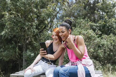 Cheerful young woman taking selfie with redhead female friend sitting at park on sunny day - DSIF00143