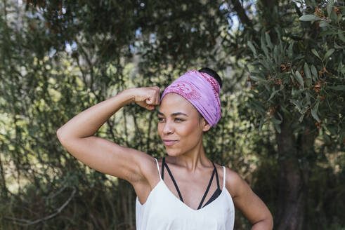 Young woman with purple bandana flexing bicep muscles while standing against plants at park - DSIF00146