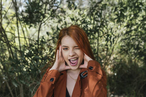 Playful young redhead woman winking while standing at park - DSIF00152
