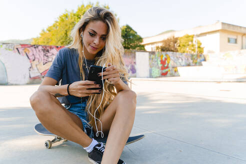 Young blond woman using smart phone while sitting with skateboard at park - FMOF01179