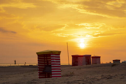 Striped tents at beach against orange sky during sunset - WIF04336