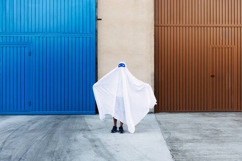 Faceless child in white ghost costume frightening with outstretched arms while standing in city during Halloween - ADSF15875