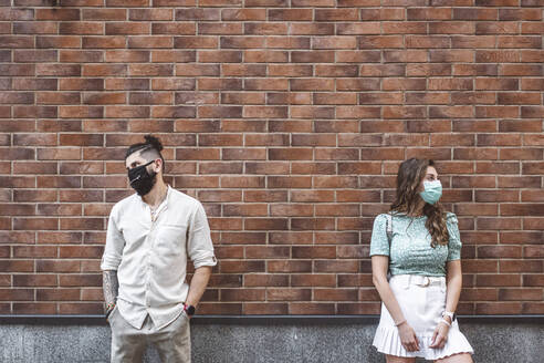 Sad couple in protective face masks standing against brick wall during coronavirus crisis - EYAF01341