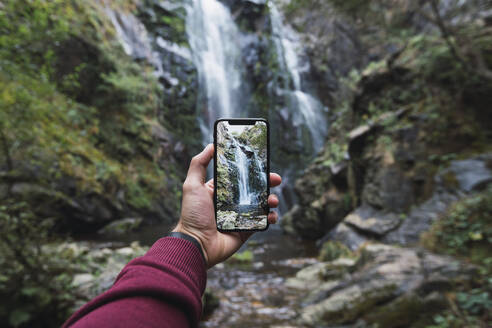 Hand of man holding smart phone while photographing famous Fervenza do Toxa in forest, Pontevedra Province, Galicia, Spain - RSGF00297