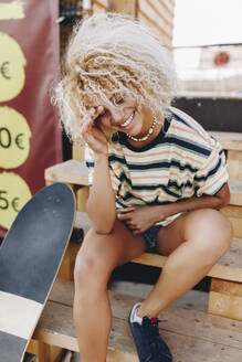 Smiling blond Afro woman sitting with skateboard on wooden steps - MRRF00534