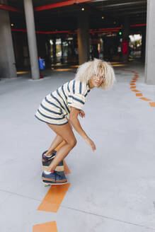 Blond Afro woman skateboarding on footpath - MRRF00537