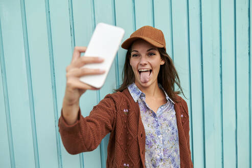 Young woman sticking tongue out while taking selfie against blue metal door - KIJF03299