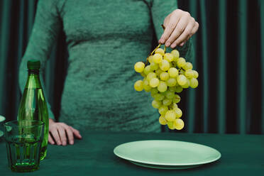 Midsection of woman holding grapes fruit while standing against green curtain - ERRF04509