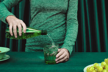 Midsection of woman pouring cocktail in glass - ERRF04512