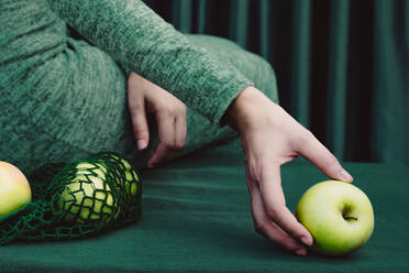 Midsection of woman green apple while sitting on table against curtain - ERRF04515
