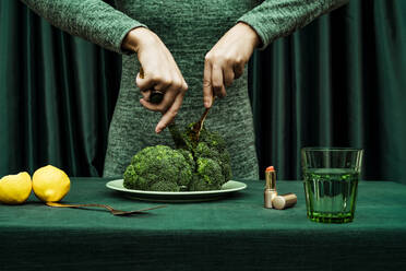 Midsection of woman cutting broccoli with knife and fork while standing against green curtain - ERRF04527