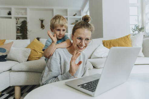 Mother and son waving hand to video call on laptop while sitting at home - MFF06215