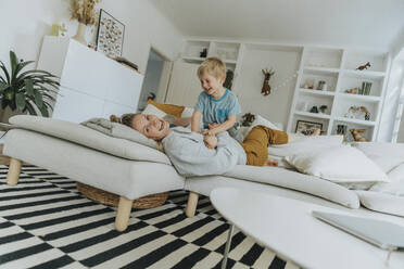 Smiling mother and boy playing on sofa at home - MFF06218