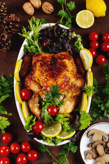 Top view of delicious roasted chicken with fresh tomatoes and parsley placed on table with lemon and mushrooms - ADSF16118