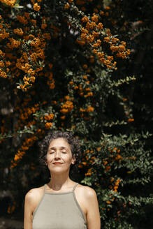 Mature woman with eyes closed standing against orange tree on sunny day - TCEF01172