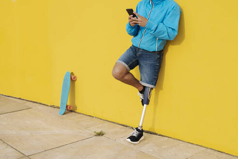 Young disabled athlete using mobile phone while standing against yellow wall - JCZF00264