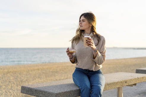 Thoughtful young woman holding fresh donut with disposable cup while sitting on bench at beach and looking away during sunset - AFVF07276