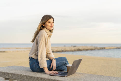 Thoughtful young woman looking away while sitting with laptop on bench at beach against sky during sunset - AFVF07282