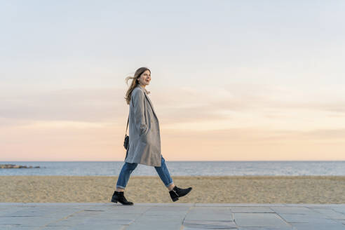 Happy beautiful woman walking on promenade at beach while looking away against sky during sunset - AFVF07297
