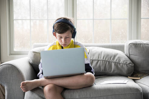 Preteen Boy Wearing Headphones Works on Laptop for Virtual School - CAVF89736