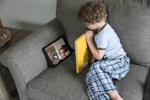 Preschool Boy Reads Book With Grandma Over Video Chat - CAVF89739