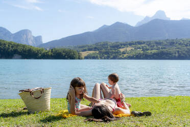 Daughters playing with mother on grass by lake - GEMF04193