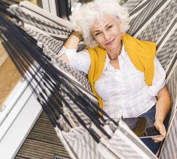 Smiling mature woman with hands behind head holding digital tablet sitting on hammock at home - UUF21628