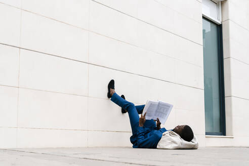 Male entrepreneur lying with duffel bag on sidewalk while reading book in city - EGAF00801