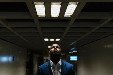 Male entrepreneur looking up while standing under illuminated light in subway - EGAF00822