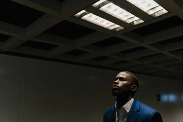 Male entrepreneur standing under illuminated fluorescent light in subway - EGAF00825
