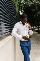 Businessman drinking from cup while using smart phone and leaning on surrounding wall - EGAF00840