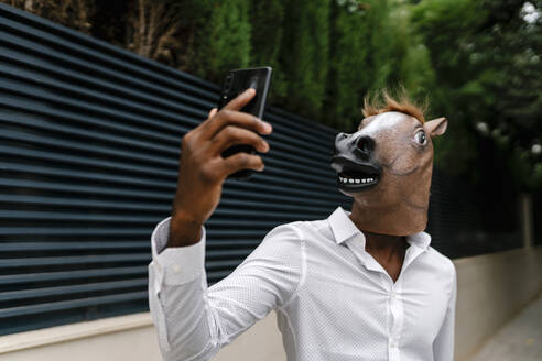 Businessman wearing horse mask while taking selfie from smart phone in city - EGAF00849