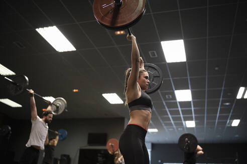 Women and men exercising with barbell while standing in gym - SNF00552