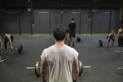 Man standing with athletes exercising in background in gym - SNF00555