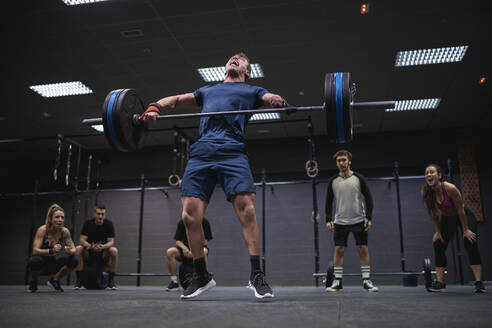 Adaptive athlete jumping while lifting barbell with people cheering in background at gym - SNF00561