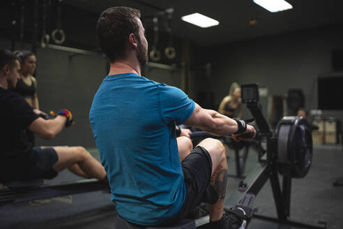 Man using rowing machine with people exercising in background at gym - SNF00567