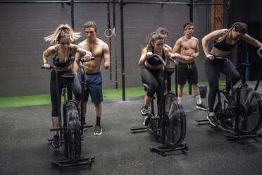 Men motivating women exercising on fitness bike at gym - SNF00570