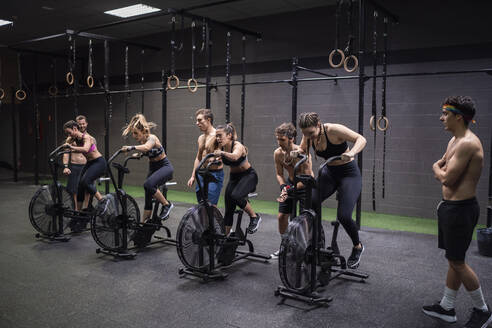 Athletes exercising on fitness bike at gym - SNF00573