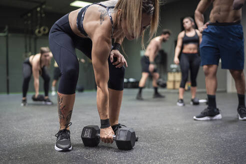 Woman picking dumbbell with people exercising in background at gym - SNF00576