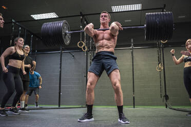 Athlete cheering man picking barbell up to shoulder while standing at gym - SNF00588