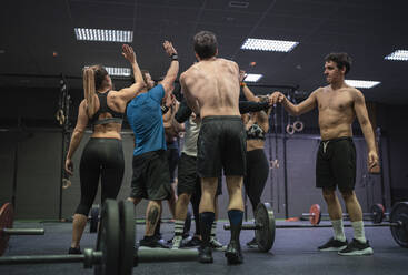 Group of athletes giving high five while standing at gym - SNF00591