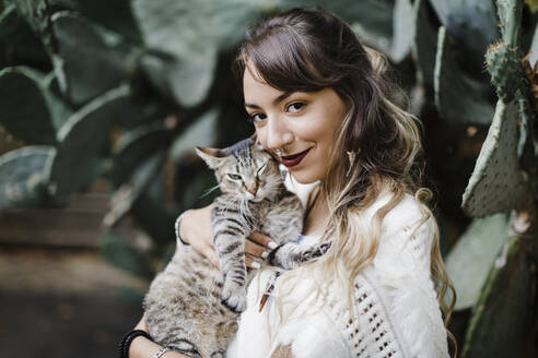 Young woman smiling while holding cat against plant - DCRF00918