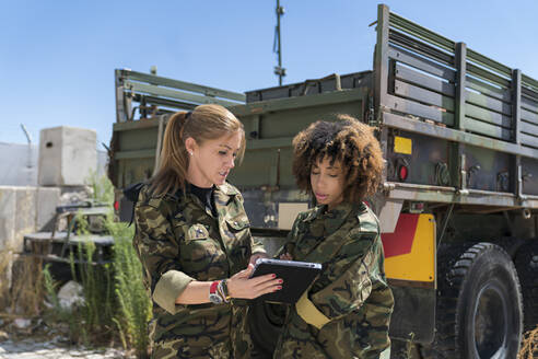 Multi-ethnic female army soldiers discussing over digital tablet at military base on sunny day - MTBF00677